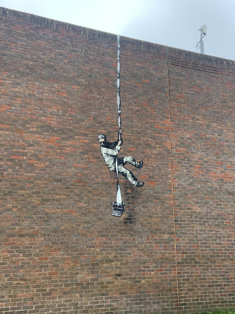 An image of Bansky's artwork, Create Escape, depicting a figure escaping Reading Gaol.