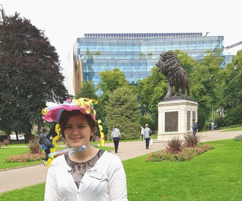 Reading Museum intern Diana dressed in a bonnet in Forbury Gardens, with the Forbury Lion statue in the background.