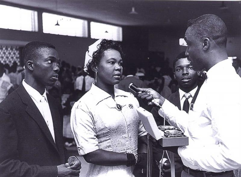 nformation Officer Gladstone Holder interviews -a couple at Seawell Airport before they Leave for the UK