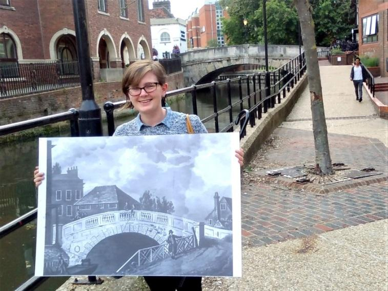 Reading Museum intern Diana standing in front of a bridge over the Kennet, holding a poster of an old print of the same bridge.