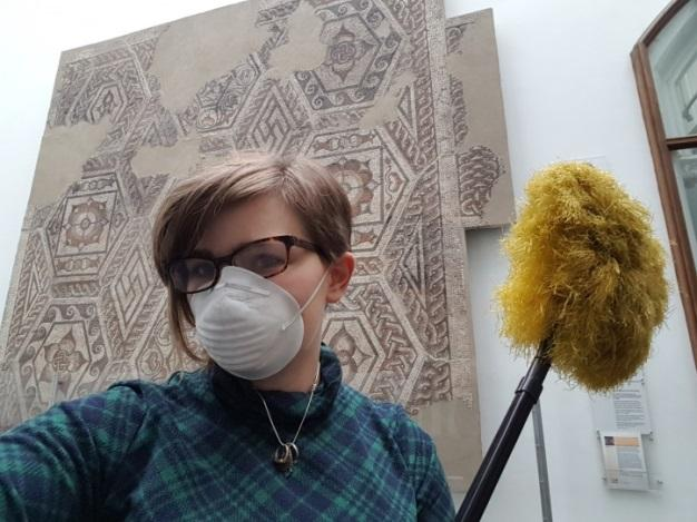Reading Museum intern Diana wearing a surgical mask as she deep cleans the galleries.