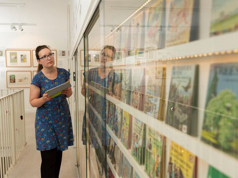 A woman researching Ladybird Books arranged on shelves.