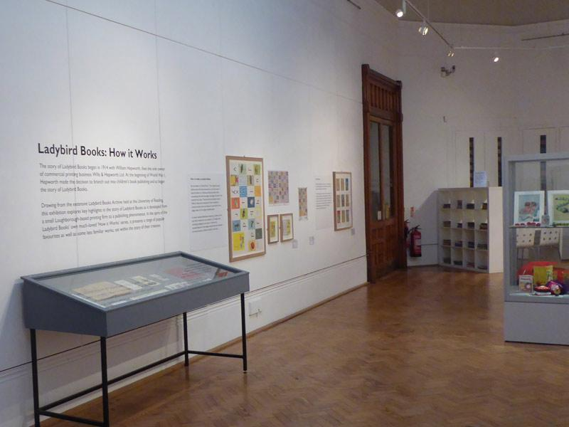 A museum gallery with Ladybird Books artworks on display.