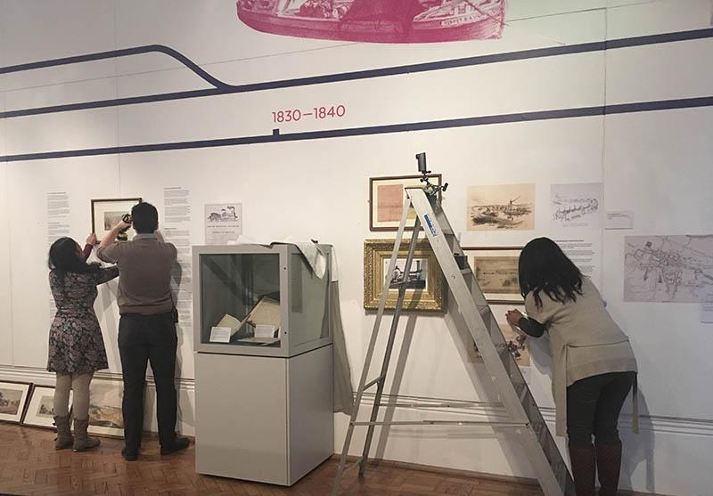 Two Reading Museum staffmembers on the left of the picture taking framed pictures off the white wall of an exhibition, with Charlene on the right of the image doing the same.