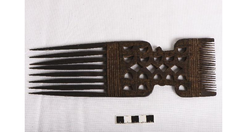 A wooden african comb on a white background.
