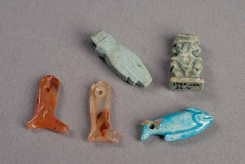 Small amuletic figures from Egypt. Clockwise from top left; faience hand, green faience figure of the god Bes, blue faience fish, stone leg and a carnelian leg.