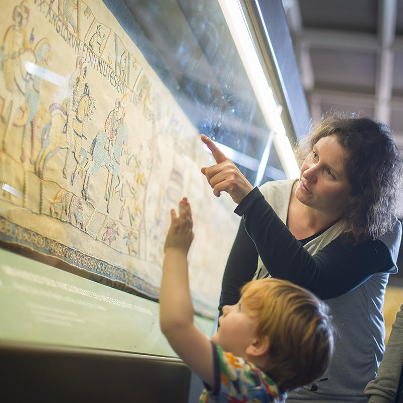 mother and child examine the Bayeux Tapestry