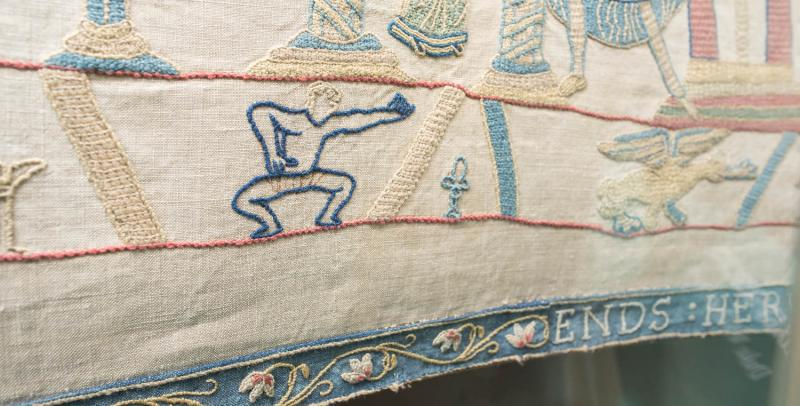 Reading Bayeux Tapestry border showing man in pants