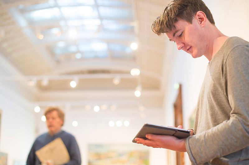 A young, white man in a grey shirt holding an iPad in an art gallery.
