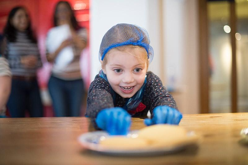 A young, white girl in a blue hairnet reaches towards the camera for some unfinished bread dough on a table.