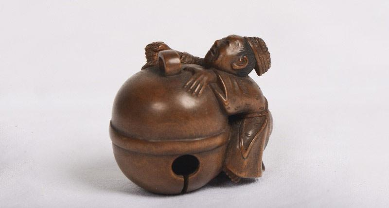 A netsuke of a man hugging a bell.