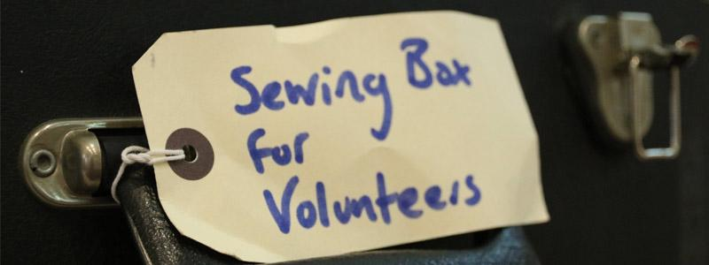 A label with 'Seqing box for volunteers' written on it in blue marker, attached to the handle of a black suitcase.