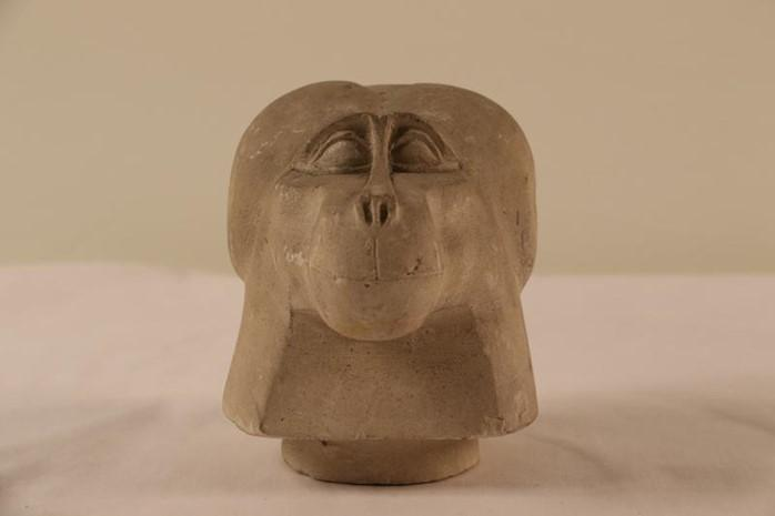 A limestone canopic jar lid in the form of a baboon's head from Abydos, Egypt.