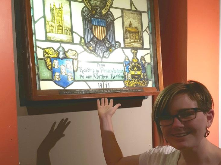 Reading Museum intern Diana standing in front of a stained glass window donated by the town of Reading in Pennsylvania, USA, to Reading, England.