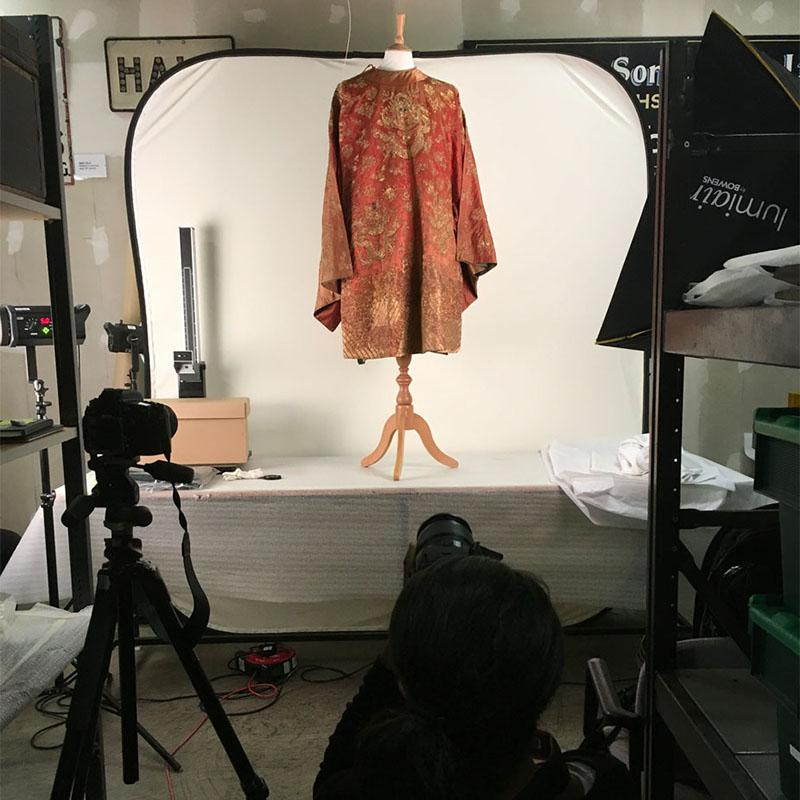 An orage Kimono on a mannequin, standing on a table covered in white tissue paper. It is the only thing illuminated in a dark room, with Charlene crouched taking a photo in the foreground.