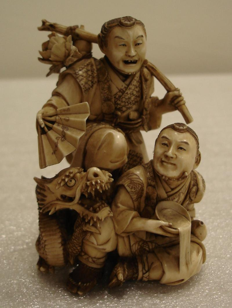 Ivory Okimono from Japan carved with two humans and a dragon