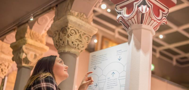 Woman looks at cloister reconstruction