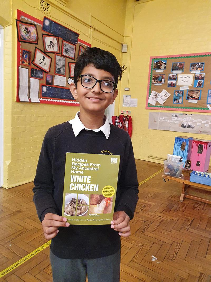 A student with a recipe card from the Hidden Recipes from the Ancestral Home project.