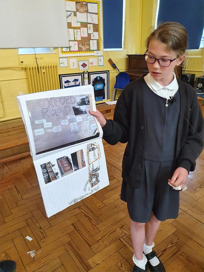 A student with a timeline showing the Oxford Road's history.
