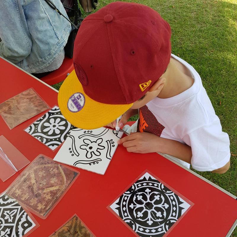 A child in a red hat painting a tile