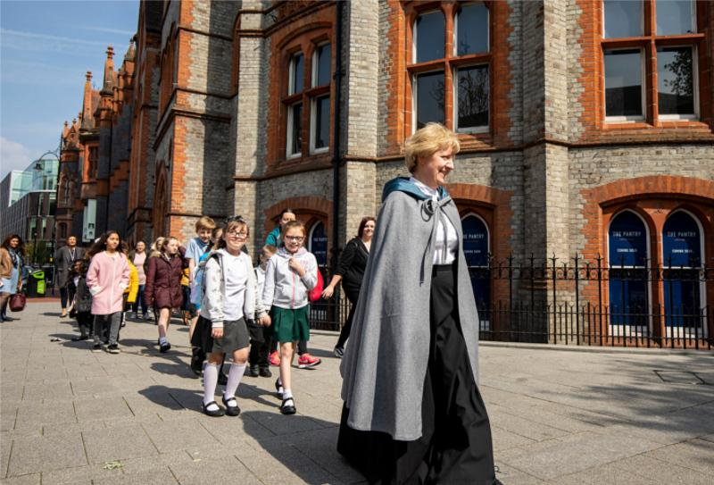 A Victorian Session Leader walking children to the schoolroom