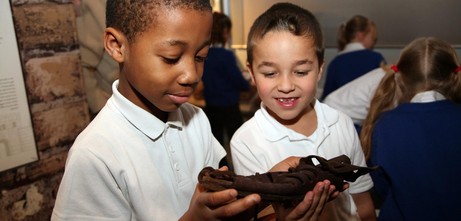 Two boys looking at a replica Roman Shoe