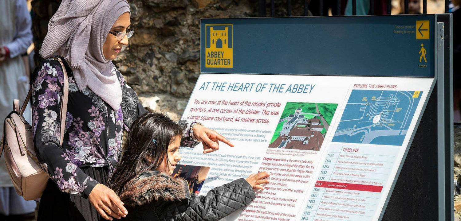 A woman and a child look at an information panel