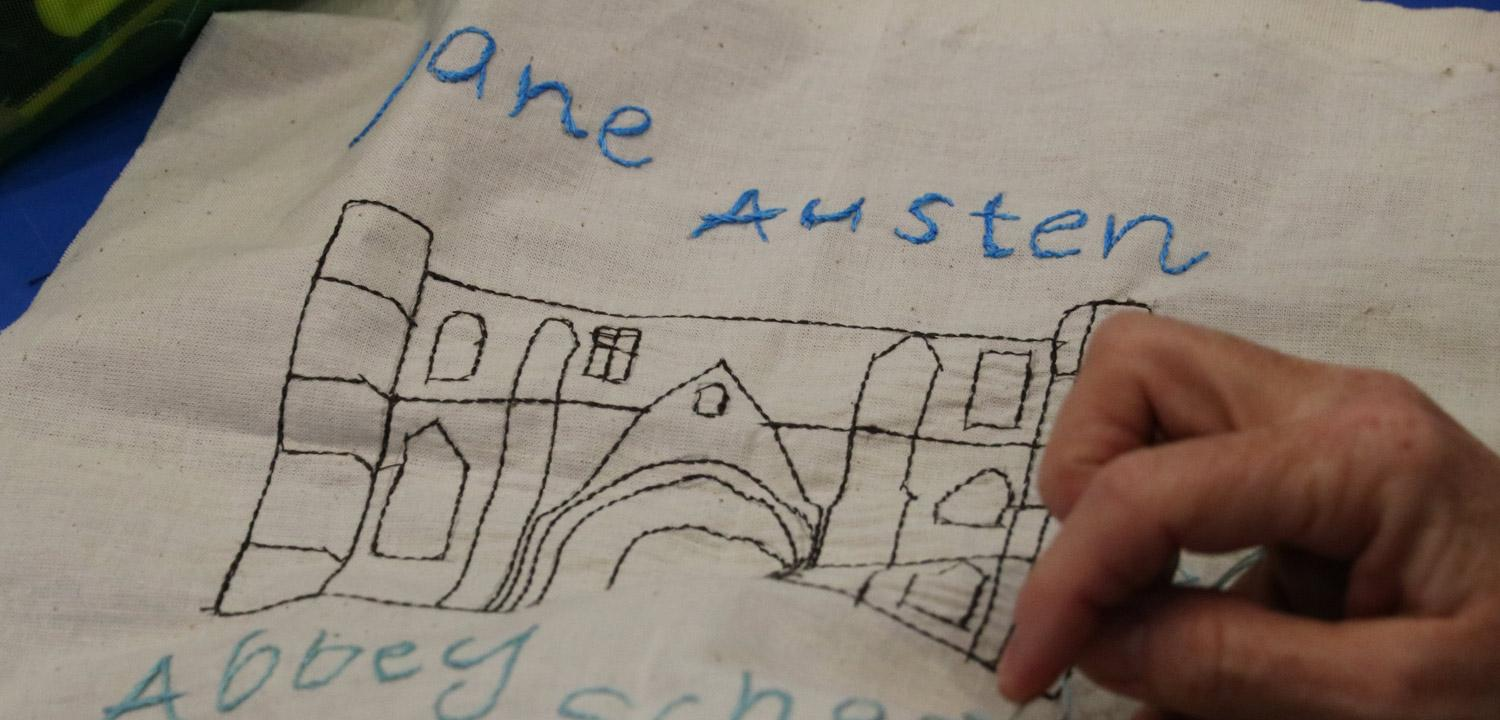 A square piece of white cloth, with the text 'Jane Austen' above a stitched outline of a medieval gateway and 'School room' stitched below it.