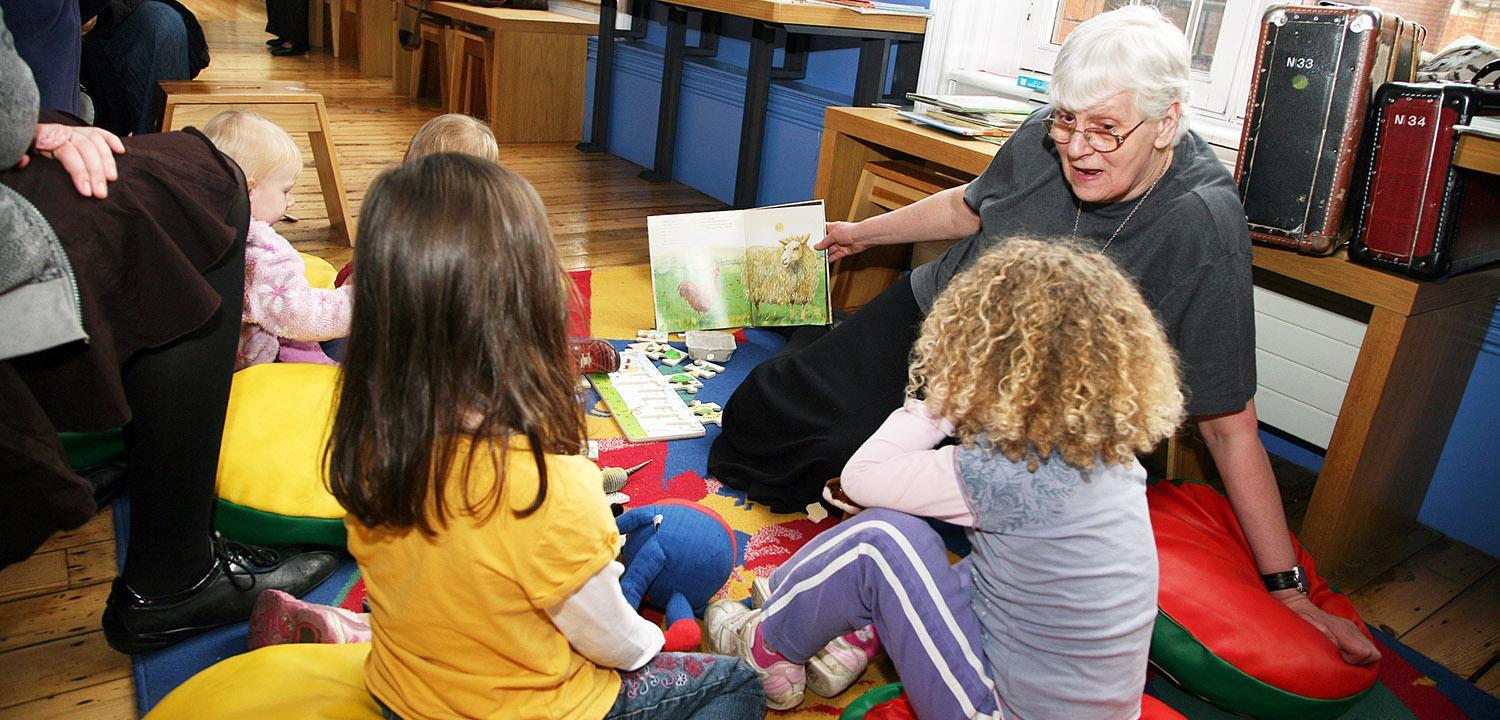A person reading a story to children