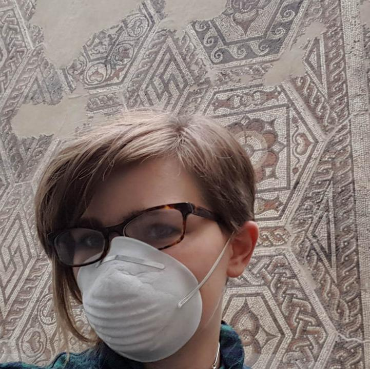 Reading Museum intern Diana standing in front of a Roman mosaic on a wall, wearing a dust mask and holding a yellow feather duster.