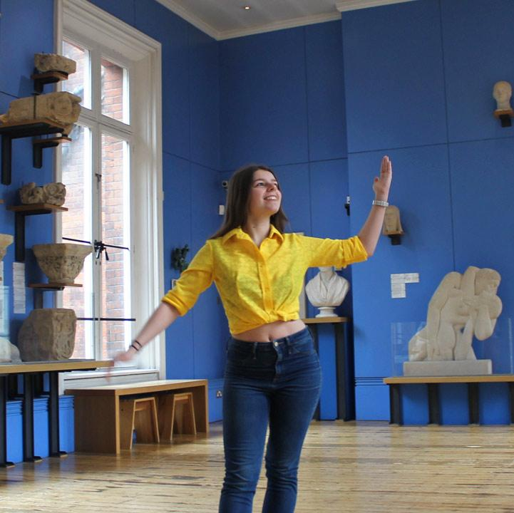 A young woman posing in a gallery of sculptures.