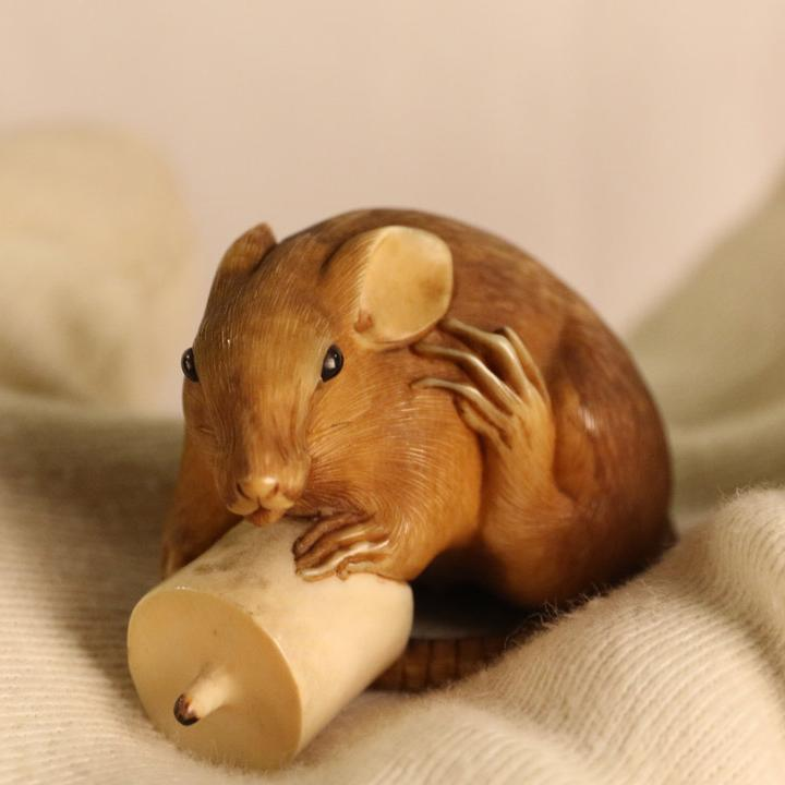 An ivory netsuke of a rat holding a candle.