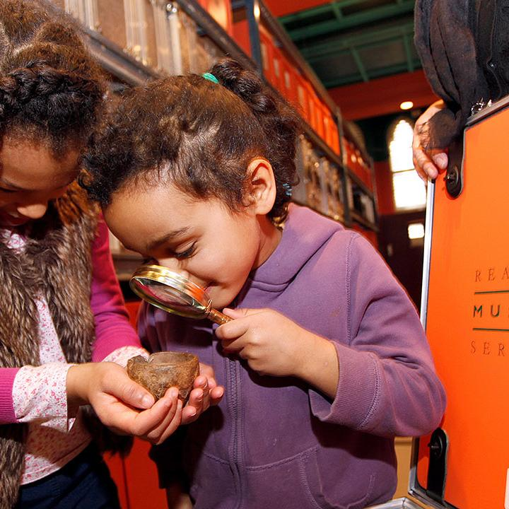 children exploring objects in a loan box