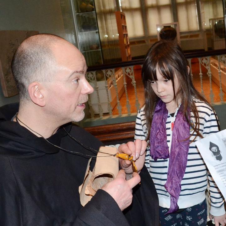 Re-enactor monk talking to children.