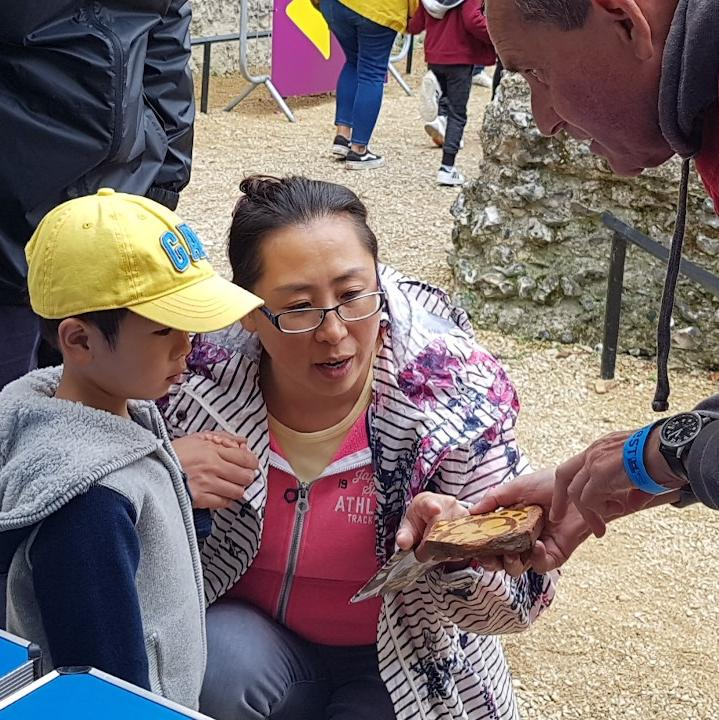 A man in a red t-shirt shows an Abbey Tile to a woman and a young boy