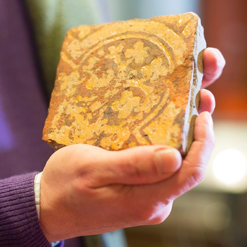 person handling a medieval tile